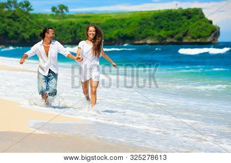 Happy Family On Honeymoon Holiday - Just Married Young Couple Having Fun, Run By Water Edge Along Se