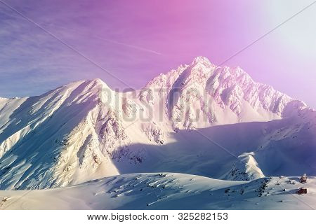 Dramatic Scenic Pink To Purple Sunrise In Austrian Alpine Mountain Peaks Covered With Snow Layer In