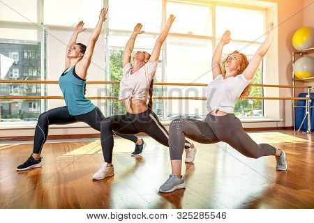 A Group Of Sporting Young People In Sportswear, In A Fitness Room, Doing Push-ups Or Planks In The G