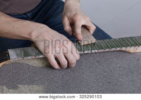 The Master Polishes The Frets On The Fretboard Of The Guitar. The Fingerboard Is Protected By Molar