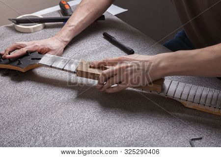 The Master Polishes The Frets On The Fretboard Of The Guitar.