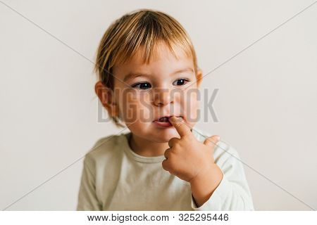 Toddler With Finger In Her Mouth. Teething Snore Gums Concept. Sucking Finger