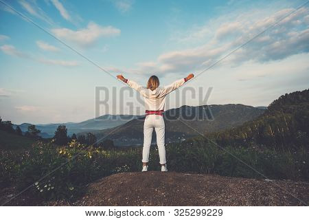 Happy Celebrating Winning Success Woman In White Clothes Standing Elated With Arms Raised Up Above H