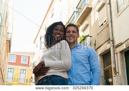 Happy Interracial Couple Enjoying Weekend Outside. Young Man And Woman Standing In Old Town Street,