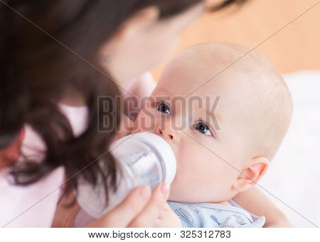 Mother Feeds Her Baby Infant From Bottle