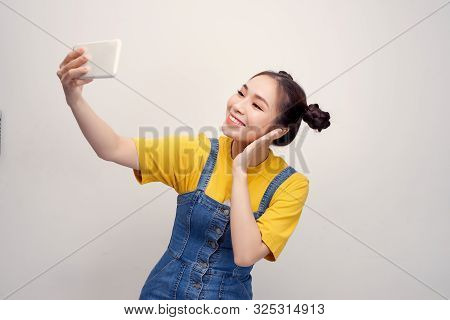 Young Asian Woman Wearing A Jeans Dungaree Who Taking Selfie