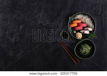 Sushi Sashimi Nigiri Set On Dark Stone Slate Background. Seaweed Wakame Salad, Salmon, Tuna, Mackere