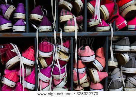Colorful used high top trainers, plimsoles or training shoes in a locker room or a second hand thrift store or charity shop