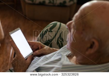 Elderly Man Is Using His Smartphone At Home. Close Up