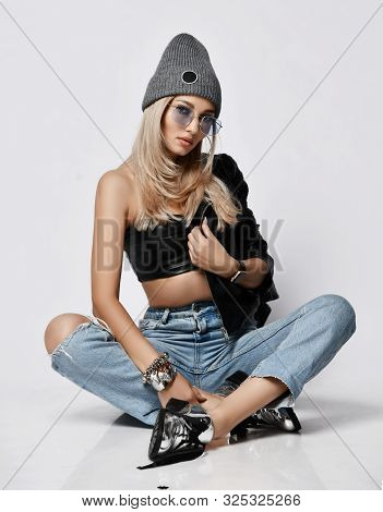 Young And Daring Grunge Style Blonde Woman In Torn Blue Jeans, Leather Top, Brutal Boots And Winter