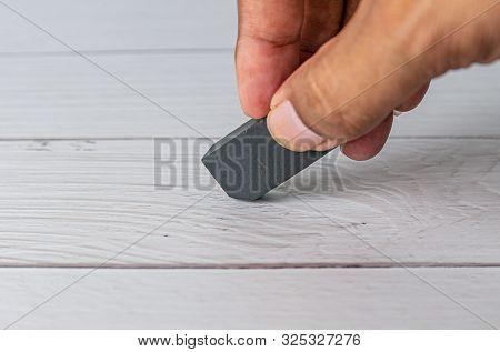 Eraser And Error Concept, Hand With Black Eraser On White Table, Mistake Erase Concept