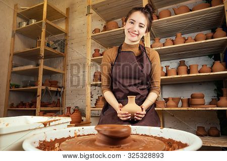 A Young And Cheerful Woman Sculpts From Clay. The Potter Works In A Pottery Workshop With Clay. The