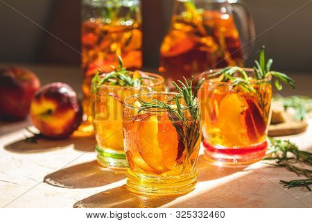 Glasses With Drops Of Sweet Peach Iced Tea, Summer Cold Peach Fizz Cocktail With Rosemary. Sunny Lig