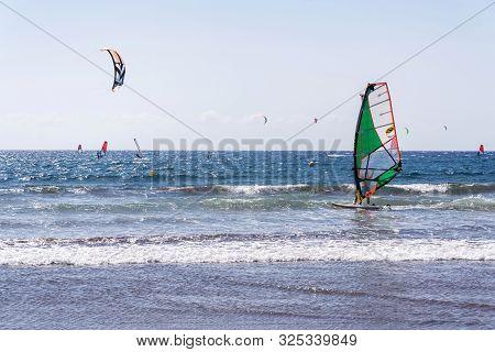 El Medano, Spain - July 7 2019: People Surfing, Kiting And Windsurfing On Playa De Leocadio Machado