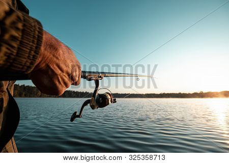 Hands Of A Man In A Urp Plan Hold A Fishing Rod, A Fisherman Catches Fish At Dawn. Fishing Hobby Vac