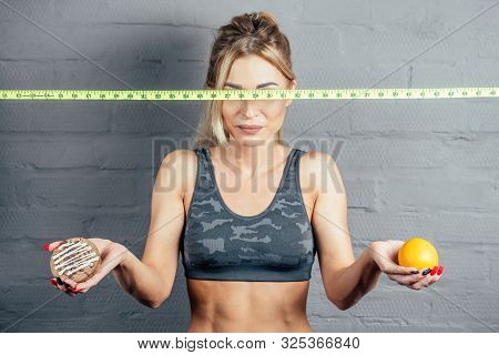 Portrait Of A Beautiful Blond Woman In A Sexy Camouflage Sports Suit With A Measuring Tape Makes A C