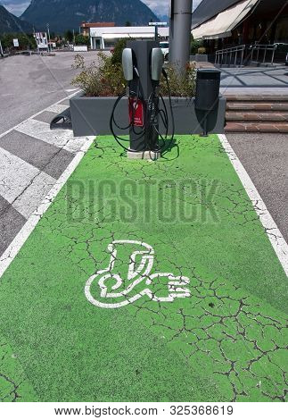 Electric Vehicle (ev) Charging Station Parking Spot With Icon  Text On Aging Green Painted Pavement.