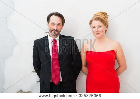 Positive mood. Waist up of adorable elegant couple expressing kindness while standing closely to each other with hands kept behind their back. Couple on white wall poster
