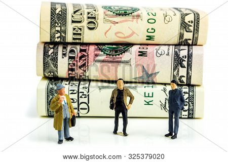 Miniature Figurines Of Businessmen Standing In Front Of American Dollar Banknotes And Making Economi