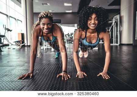 Fit African Girls In Gym Doing Plank Exercise For Back Spine And Posture In Gym. Concept Pilates Fit