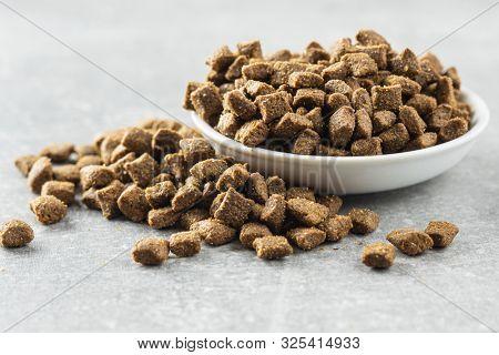 Dry pet food. Kibble dog or cat food in bowl.