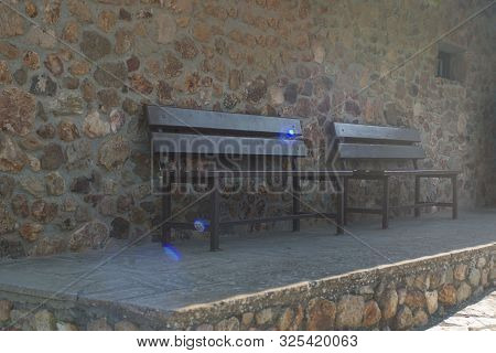 Two Wooden Benches Near The Stone Wall Of The Stavrovouni Monastery In Bright Back Ligh, Greek Ortho