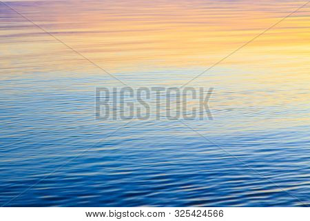 Clear Water Texture In Blue And Orange. Background Of The Ocean And The Sea Backlit By The Sun. Soft