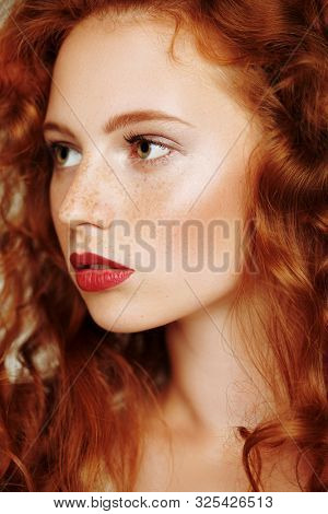 Close-up portrait of a beautiful young woman with long red hair. Hair care, hair coloring.