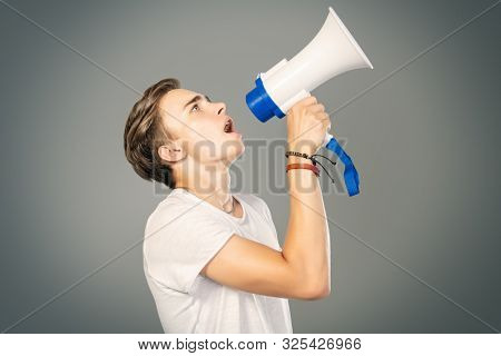 A portrait of a young goodlooking guy in a white t-shirt with a megaphone. Beauty of men, casual fashion.