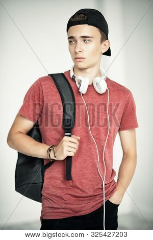 A portrait of a young goodlooking guy in a red t-shirt in the baseball cap with the headphones. Beauty of men, casual fashion.