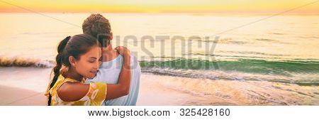 Couple in love hug banner panorama. Asian woman hugging embracing boyfriend relaxing on beach watching sunset - love and tenderness on travel summer holidays.