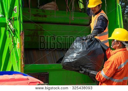 [garbage collector] Asian worker of urban municipal recycling garbage collector truck loading waste and trash bin in thailand, Trash keeper. poster