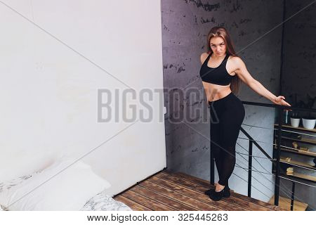 Attrctive Fitness Woman Doing Stretching Exercises At Home, As Part Of A Healthy Lifestyle Without G
