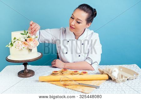 Confectioner Pastry Chef Baker Woman Decorates Creamy White Two-tiered Wedding Birthday Cake With Fr