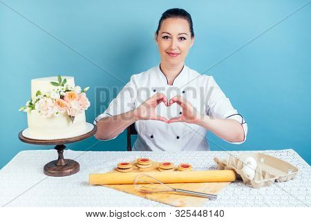 Confectioner Pastry Chef Woman Shows Fingers Heart Symbol Next To Creamy White Two-tiered Wedding Bi