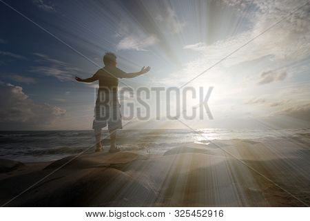 Young Man Standing On The Rock Absorb The Sunrise Power