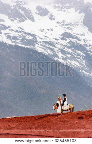 Couple Riding Horse Pointing At Yulong Snow Mountain, Yunnan, China.