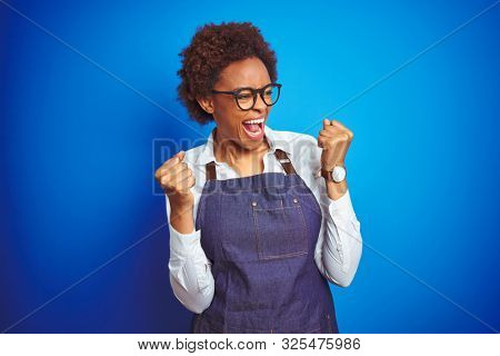 Young african american woman shop owner wearing business apron over blue background very happy and excited doing winner gesture with arms raised, smiling and screaming for success. Celebration concept