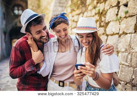 Happy Group Of Tourists Traveling And Sightseeing Using Phone.
