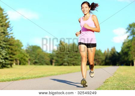 Sport fitness woman running in park on summer day. Asian female runner during outdoor workout. Fit sport fitness model of mixed Asian / Caucasian ethnicity.