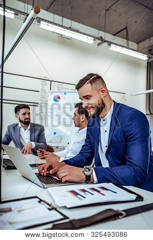 Vertical Shot Of Attractive Bearded Young Man Working On Laptop With Colleagues In Office. Confident
