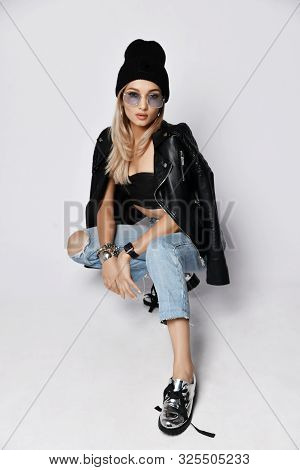 Grunge Style Girl In Torn Blue Jeans, Leather Top And Jacket With Zippers, Chrome Boots With Untied