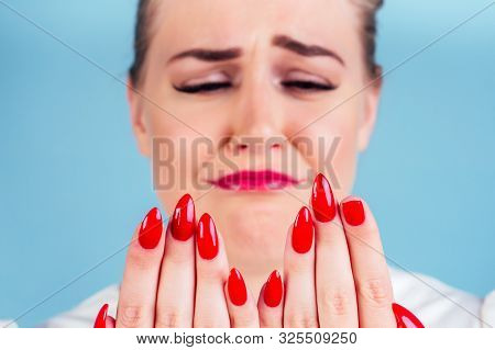Close-up Portrait Of Nervous Unhappy Young Blonde Woman Looking At A Broken Fingernail And Crying .
