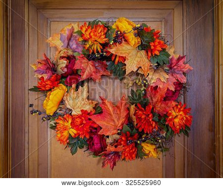 An autumn inspired wreath hanging on an old wooden door.