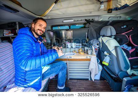 Making Breakfast Or Lunch In Campervan, Motorhome Or Rv. Young Hipster Guy Preparing Food In Camper