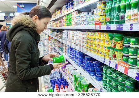 Minsk, Belarus - September 29, 2019: Man Shopping Yogurt In Grocery Store. Young Woman Reading Ingre