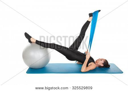 Mixed race woman in her forties Pilates training on the mat, with a ball and band isolated on white