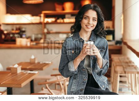 Cheerful Young Woman In Casual Outfit Smiling And Enjoying Fresh Coffee While Sitting In Cozy Coffee
