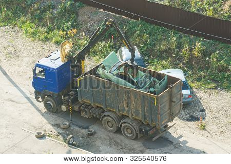 Crushed Car Being Picked Up By A Grabber. An Accident Car Has Been Loaded Onto A Dumptruck By Crane.