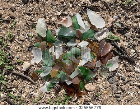 Small Pile Of Waterworn Glass Splinters Washed Up On Beach Sand